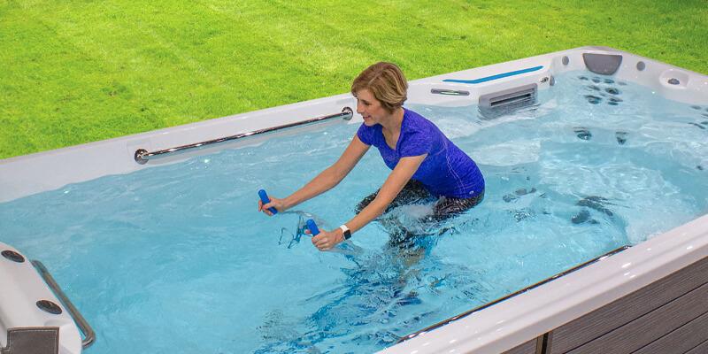 Woman using and comparing swim spa bike