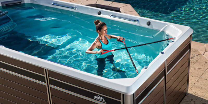 Woman considering buying and using row bars in and comparing swim spas