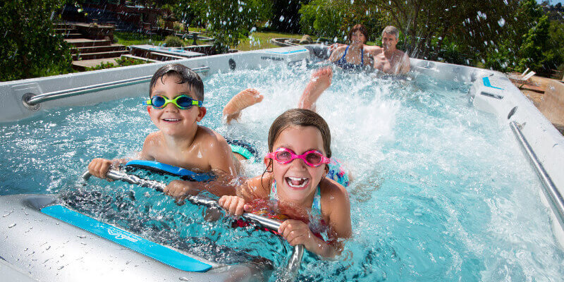 Kids and family considering buying and swimming in swim spa