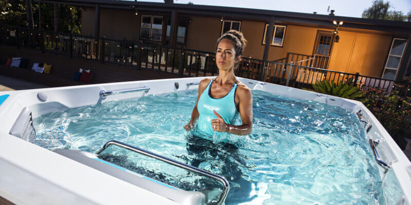 Lady considering buying and exercising in and comparing swim spas