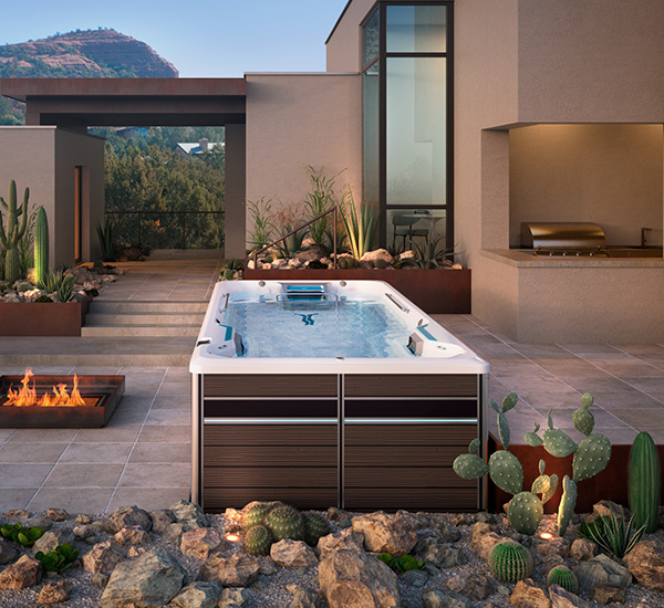 Swim spa installation next to fireplace in backyard