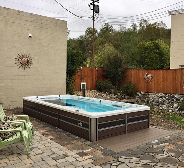 In-ground swim spa installation in back patio