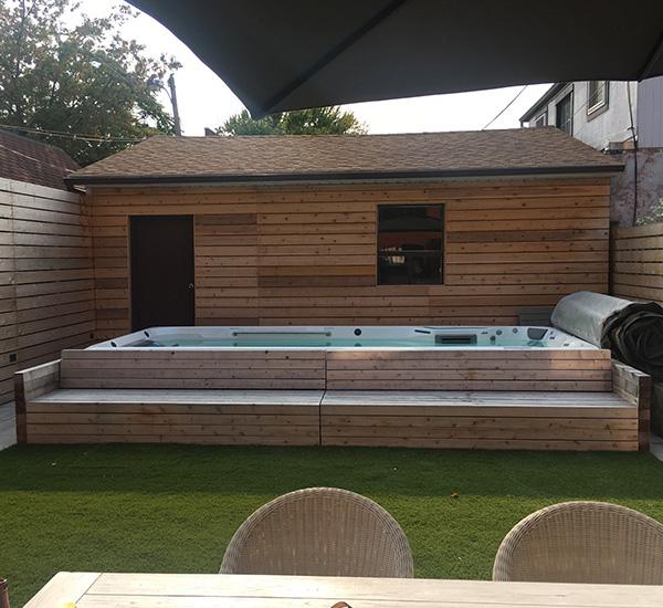In-ground swim spa installation in front of sauna