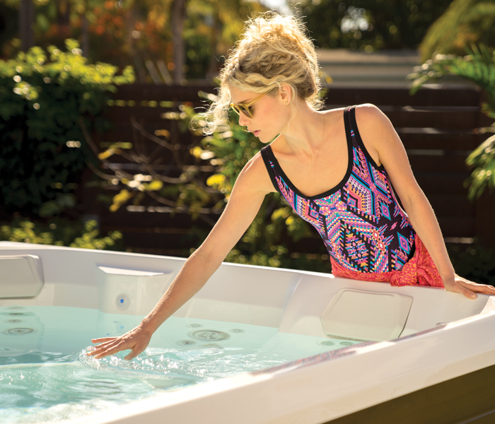Woman feeling water in hot tub water running after service in Oklahoma City