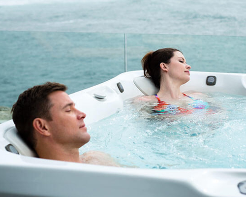 Couple enjoying low cost performance jets in hot tub